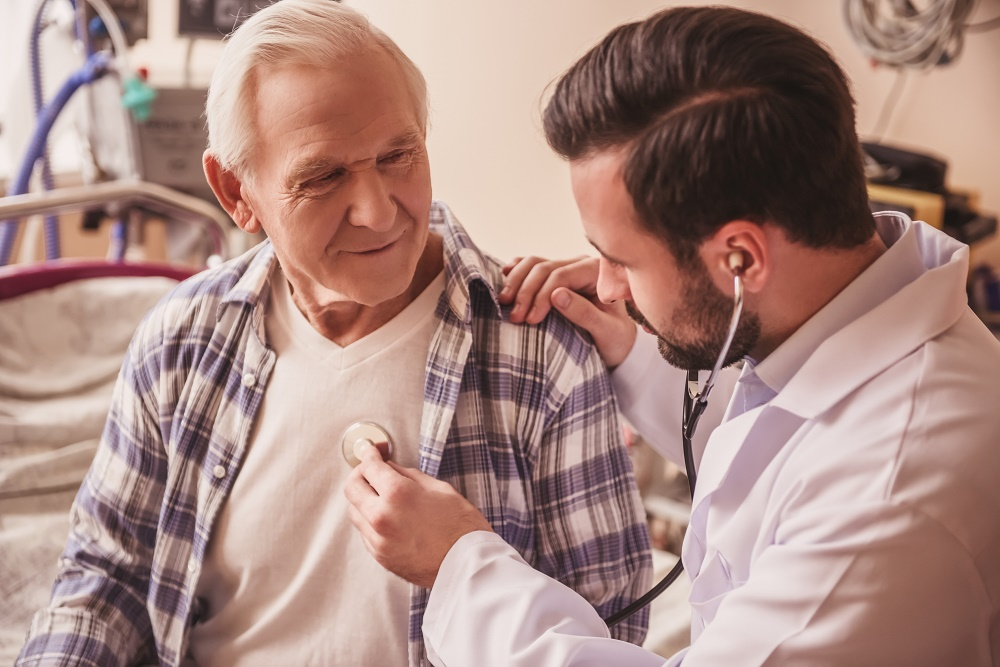 Doctor is listening to the heartbeat of a handsome old man using a stethoscope - Saddleback Men's Health Services
