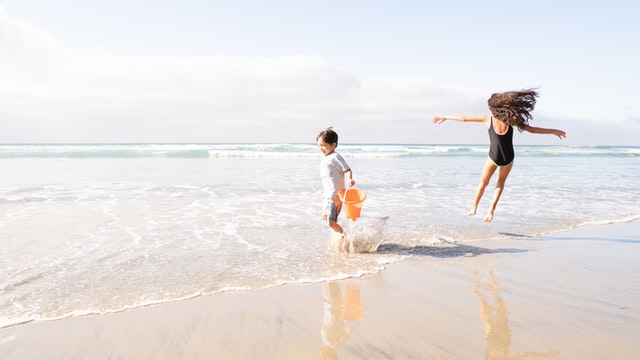 kids playing at beach wearing sunscreen for sun protection
